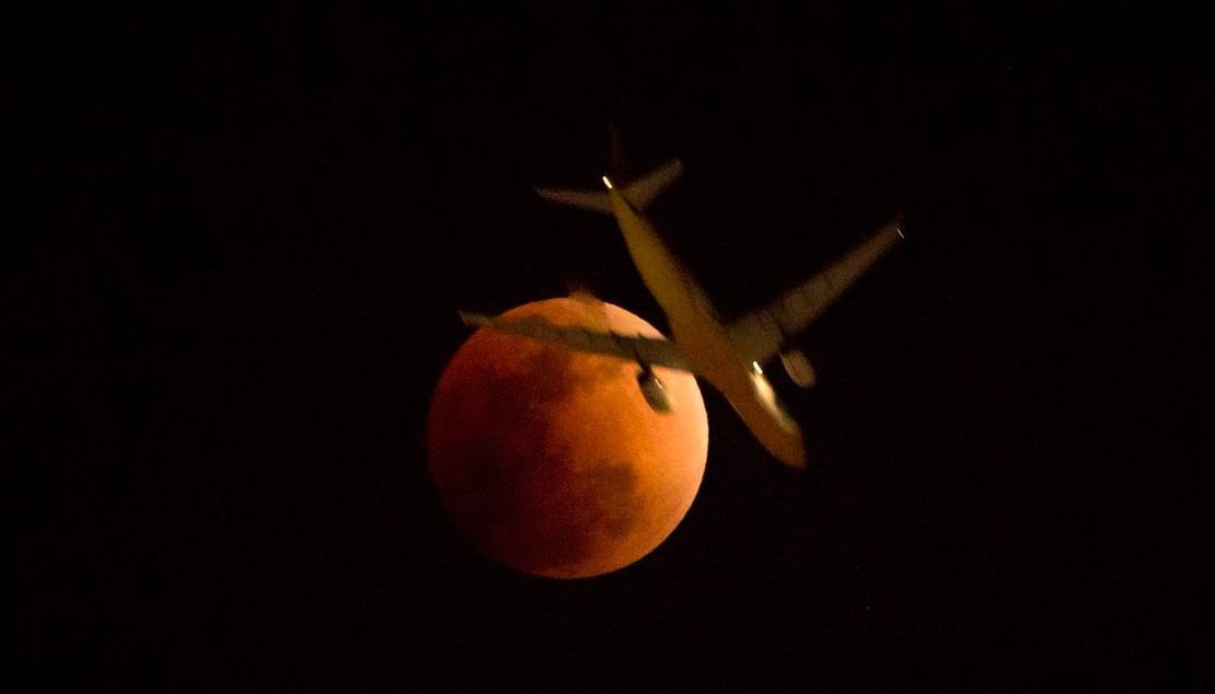 Un avión pasa delante de la luna en Hong Kong.