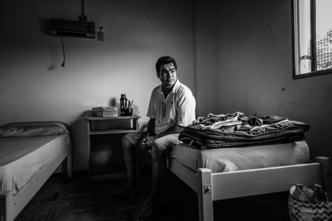 Un hombre permanece en su cama dentro del estadio Centenario, que se utiliza como refugio para unas 30 personas en situación de calle.