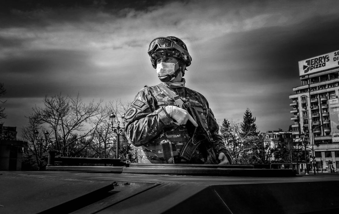 Un soldado rumano con barbijo vigila desde un vehículo militar, mientras la policía realiza controles a los autos de civiles.