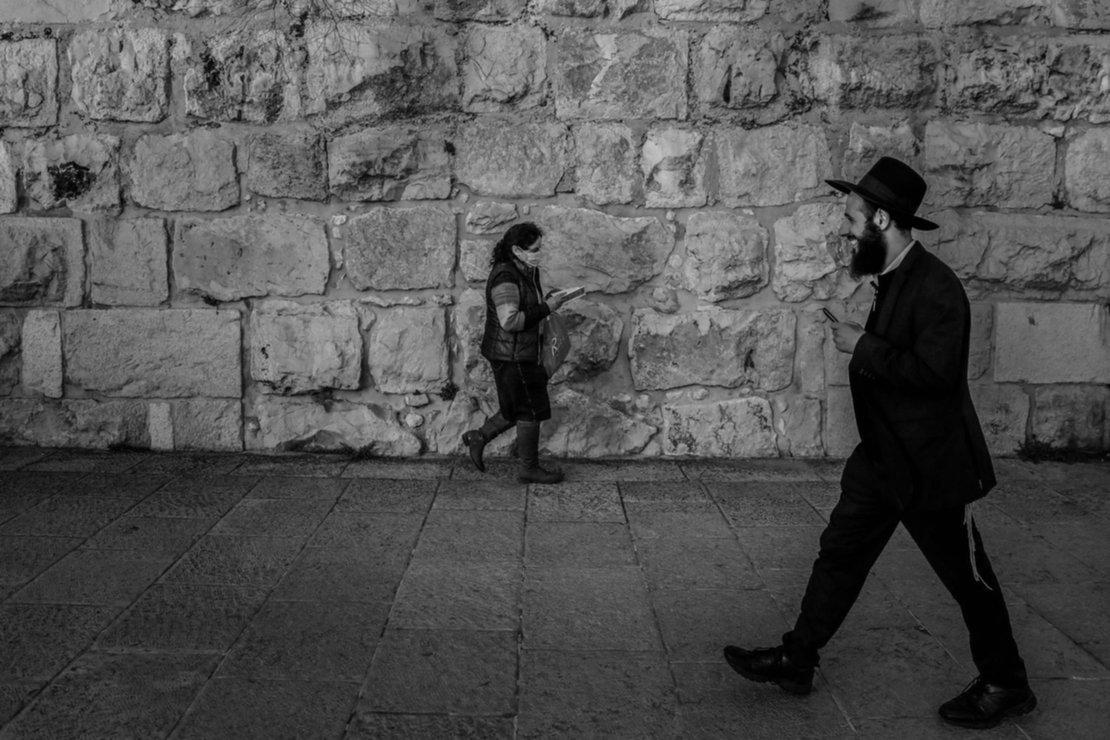 Una mujer con una máscara facial protectora y un hombre judío ortodoxo pasan cerca de los muros de la Ciudad Vieja en Jerusalén.