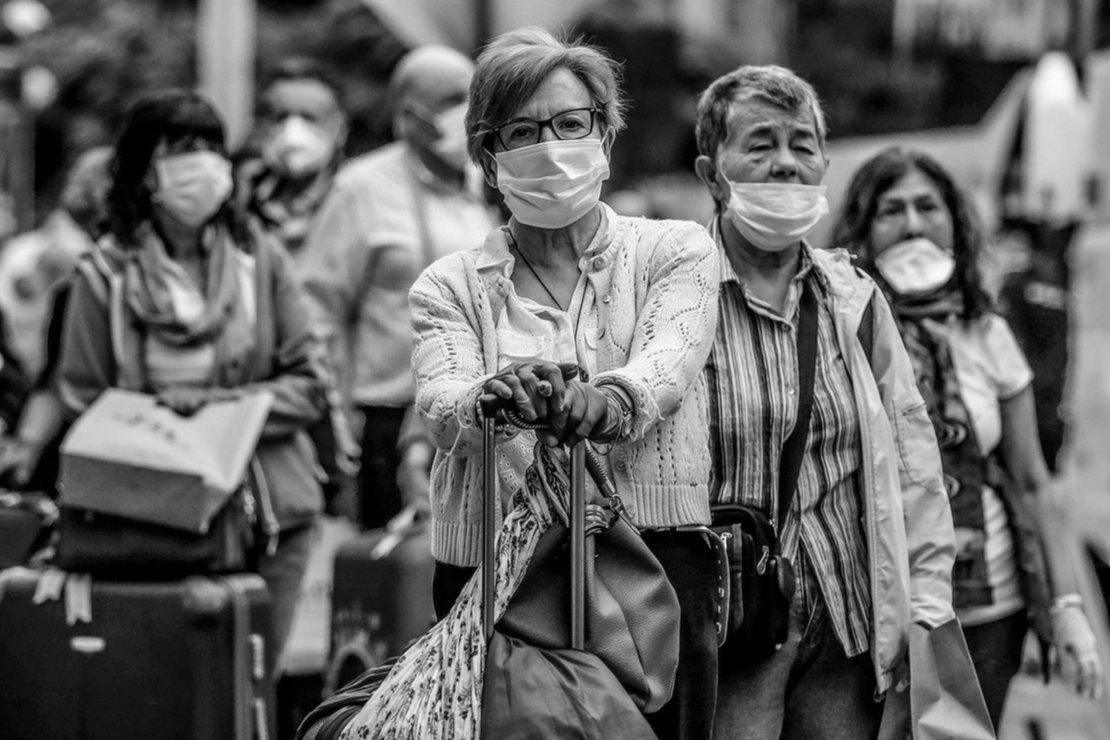 Ciudadanos españoles esperan los autobuses que los llevarán al aeropuerto a tomar un avión de repatriación de Iberia este miércoles, en Lima