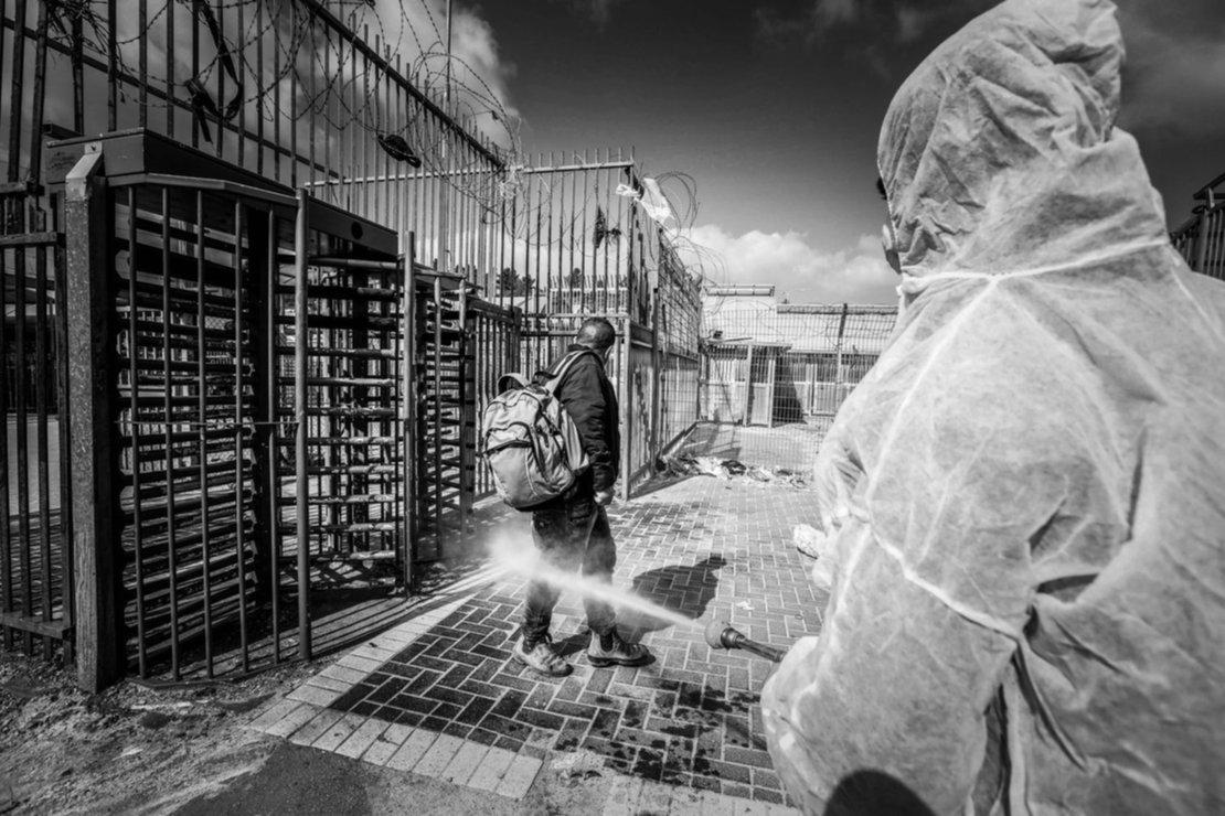Un empleado del ministerio de salud palestino desinfecta a un trabajador que regresa de Israel por la frontera.
