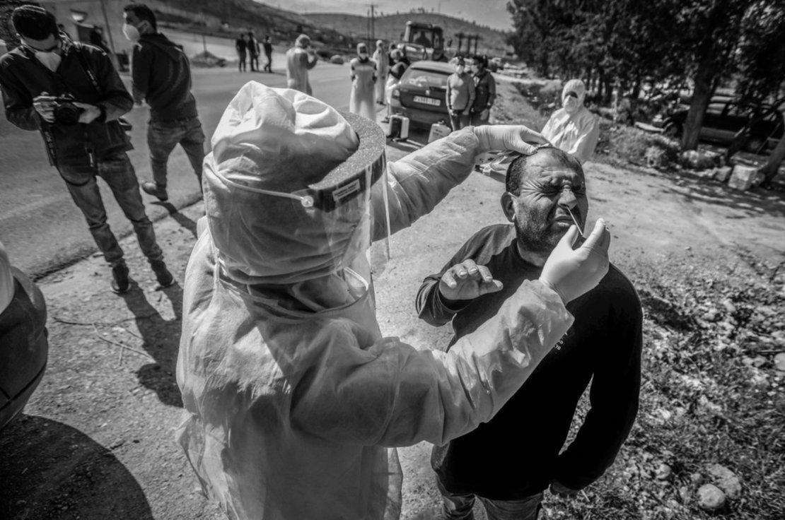 Un trabajador del ministerio de salud palestino recoge una muestra de saliva de un ciudadano.